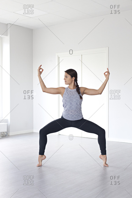 Young woman in goddess pose with hands in Jnana Mudra during yoga session in studio