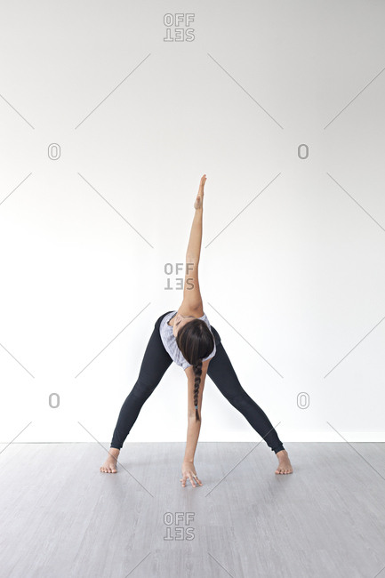 Young woman in wide legged forward bend pose during yoga session in studio