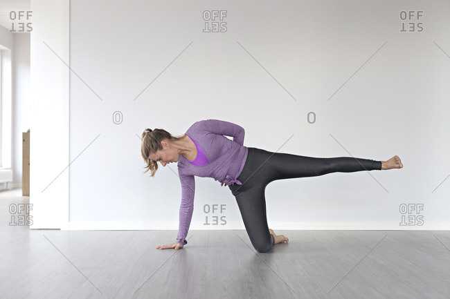 Young woman attempting balancing pose during yoga session in studio