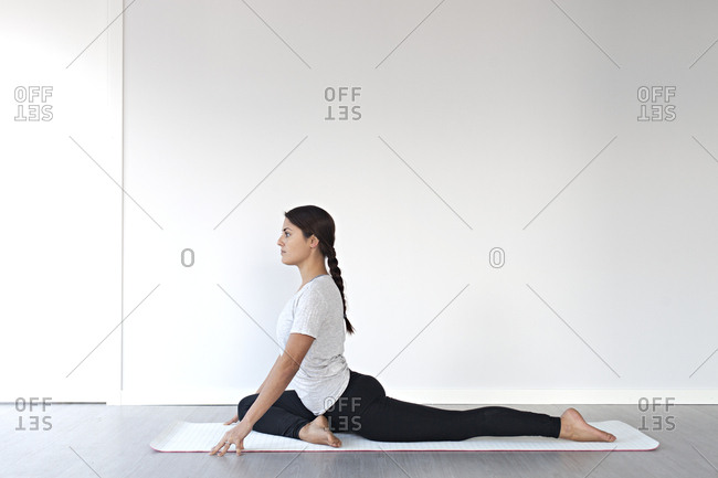 Young woman in half pigeon pose during yoga session in studio