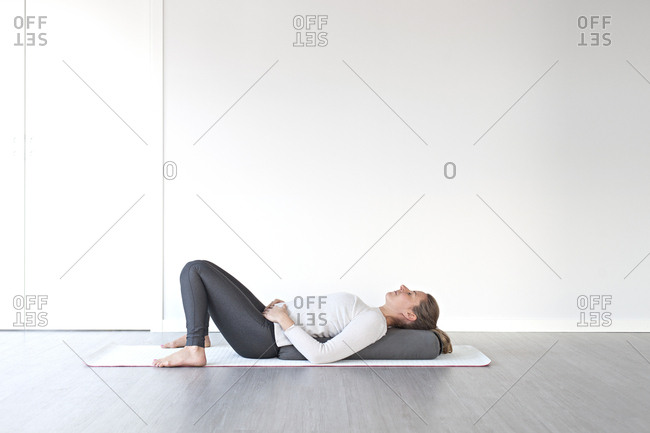 Young woman relaxing in corpse pose during yoga session in studio