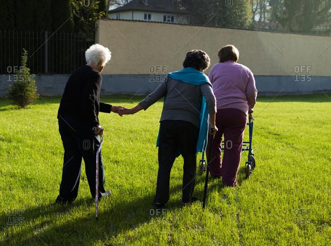 Senior women walk on a lawn