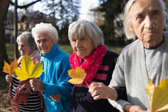 Senior women hold tree leaves outdoors