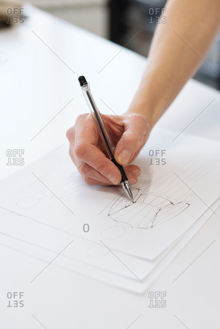 Close-up view of unrecognizable fashion designer drawing sketch of garment on sheet of paper with pen