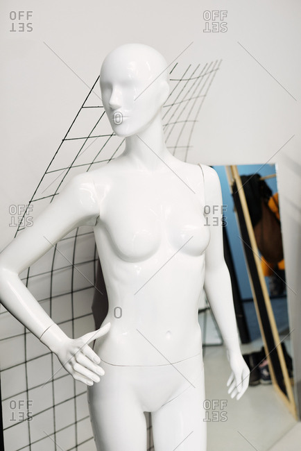 Naked female mannequin standing in atelier on white background