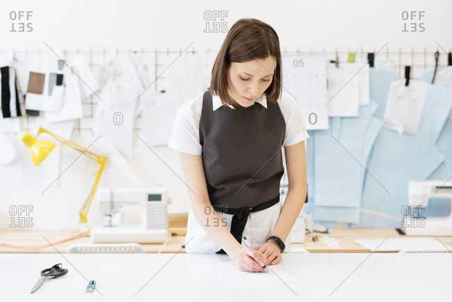 Professional female tailor standing by table and drawing sketches of new garment on background of multiple templates