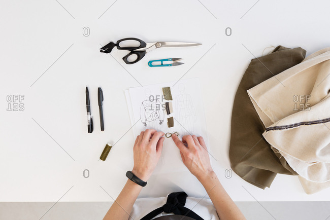 Directly above view of unrecognizable female tailor choosing right fabric for garment while standing by table with sketch