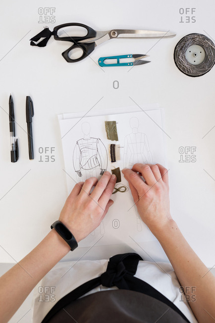Top view of unrecognizable female designer choosing textile for garment while standing by table with blouse sketch