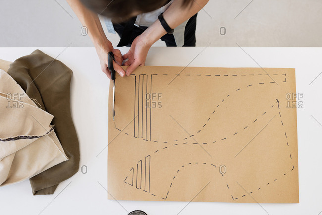 Unrecognizable female custom tailor standing by table in atelier and cutting out templates for garment, directly above view