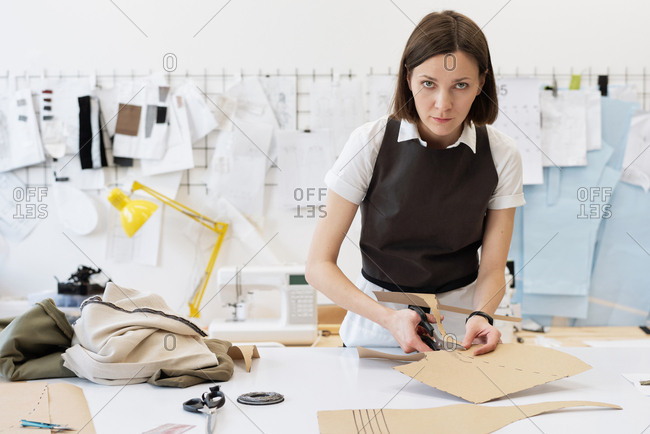 Caucasian female custom tailor cutting out sewing patterns for new clothes in atelier and looking at camera