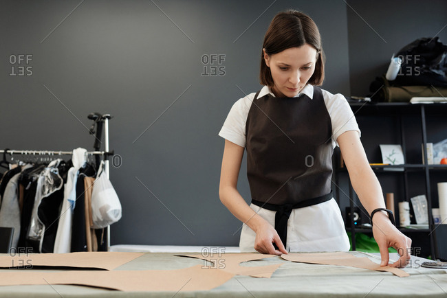 Process of creating garment. Young female tailor standing by table in atelier and putting sewing patterns on fabric