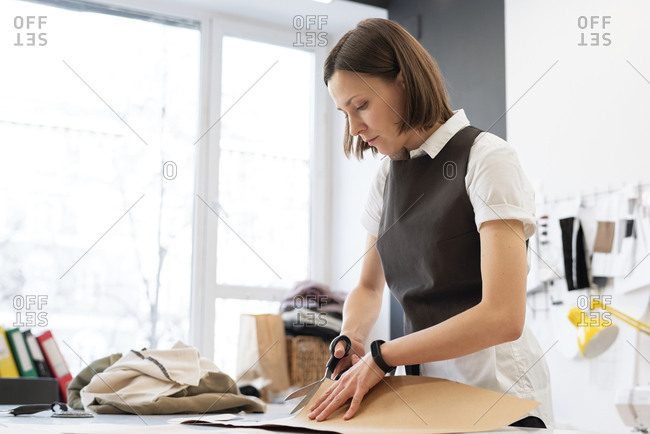 Woman working in atelier. Young concentrated female tailor cutting sewing patterns for clothing out of cardboard