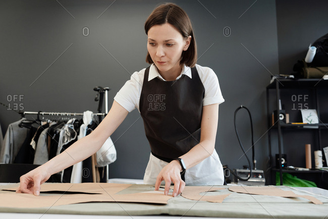 Woman working in tailor shop. Young female seamstress standing by table and placing sewing patterns on garment fabric