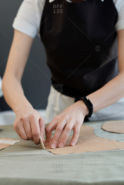 Working process in atelier. Close-up view of unrecognizable female seamstress tracing sewing templates on fabric with chalk