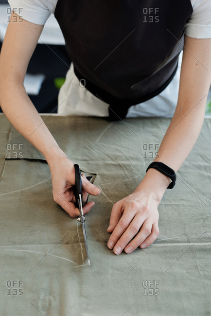 High angle view of unrecognizable female tailor cutting tracings out of fabric while standing by table in atelier