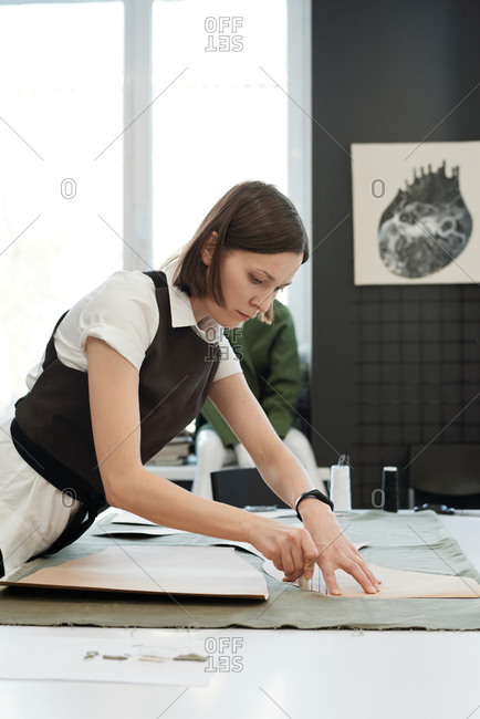 Professional custom tailor working in atelier. Young Caucasian woman standing by table and tracing sewing patterns on textile with chalk