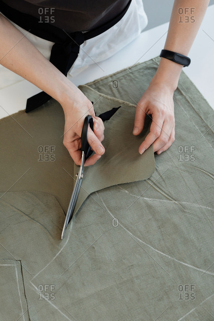 High angle view of unrecognizable female seamstress cutting tracings out of fabric in atelier