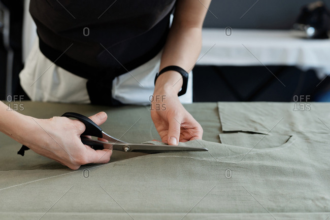 Close-up view of unrecognizable female seamstress cutting tracings out of fabric for sewing new garment
