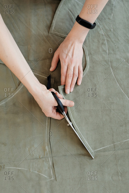Unrecognizable female tailor cutting pieces of fabric outside the tracing lines made with chalk, high angle view