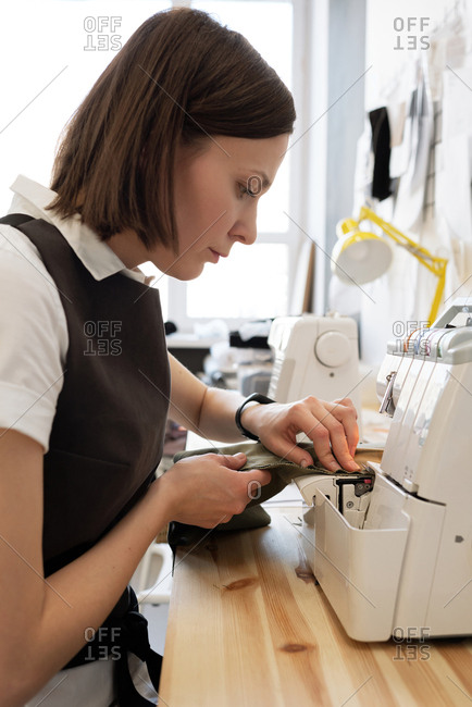 Side view of Caucasian female tailor sewing a piece of clothing on modern sewing machine in atelier