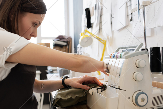 Professional female custom tailor sewing garment on modern sewing machine in atelier, side view