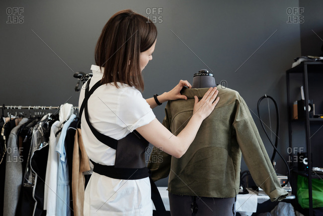 Professional female custom tailor dressing mannequin in unfinished garment in atelier