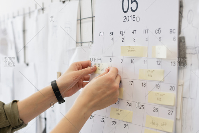 Close-up view of unrecognizable female fashion designer looking at sticky notes with plans on calendar hanging on wall