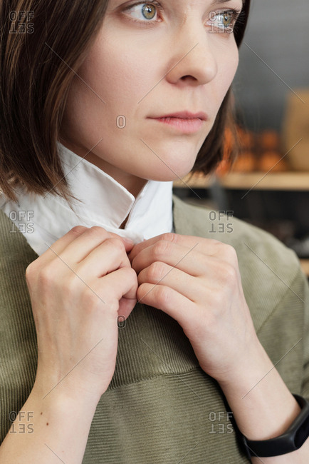 Portrait of young thoughtful Caucasian woman trying on new garment, buttoning up and looking into the distance