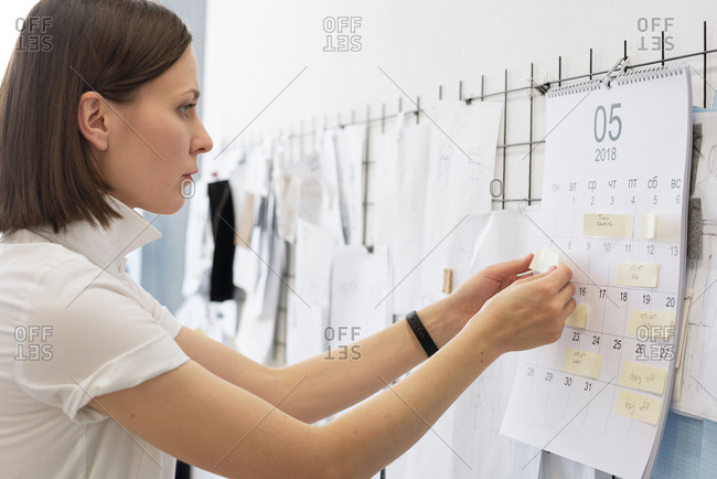 Side view of young Caucasian dressmaker planning her work for month, sticking notes to calendar hanging on wall