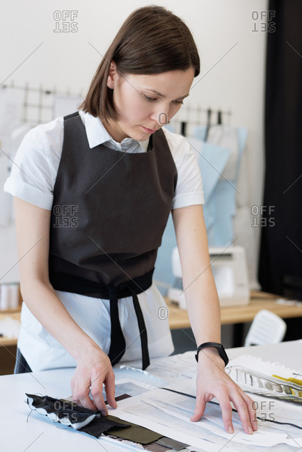 Young professional female custom tailor standing by table in atelier and choosing fabric for new garment