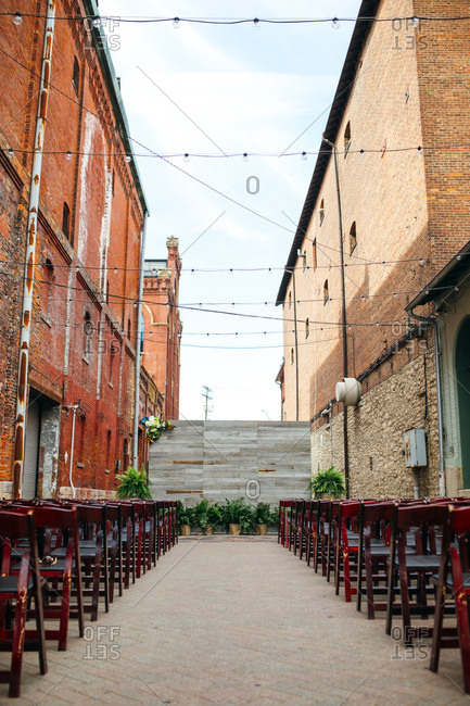 Wedding ceremony set up in an alley between brick buildings