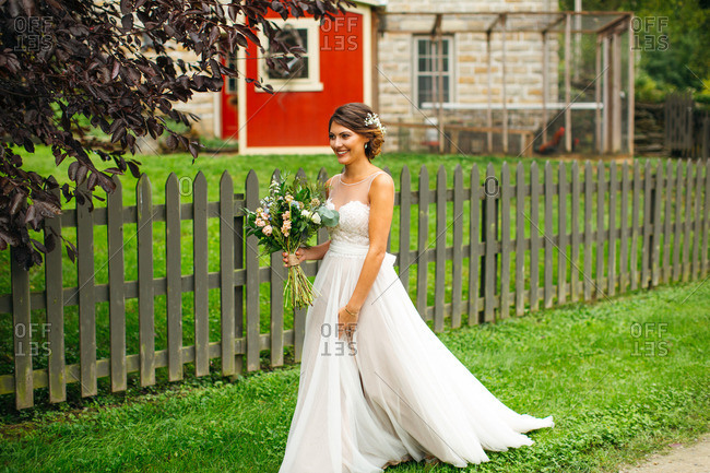 Bride walking on a farm with her bouquet