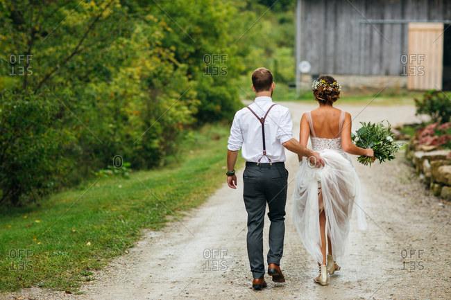 Groom carrying bride's dress train
