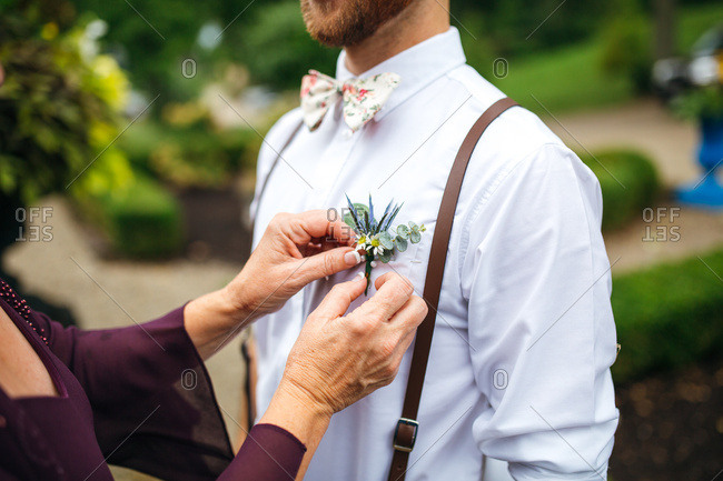Mother pinning boutonniere onto groom