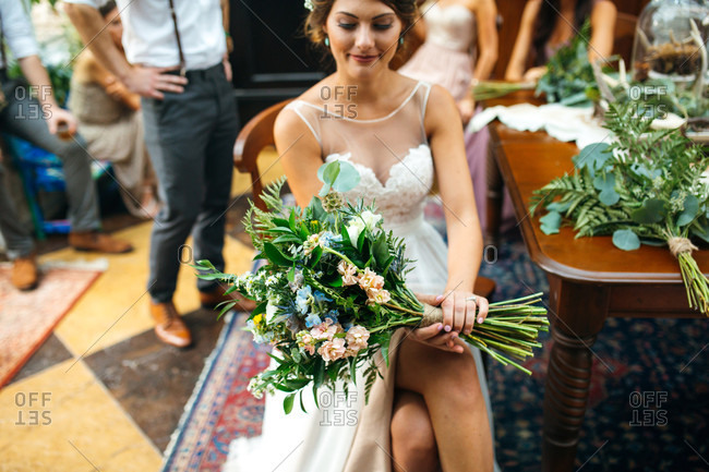 Bride sitting in chair holding her bouquet