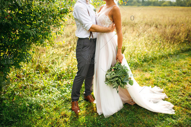 Groom and bride embraced in a field