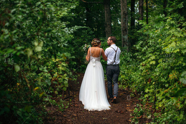 Bride and groom walking in a forest together