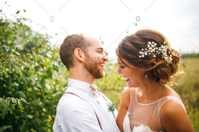 Happy groom and bride embraced in a field