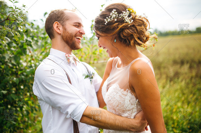 Happy bride and groom laughing in a field