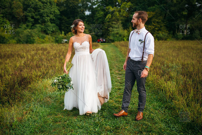 Groom and bride walking together in a field