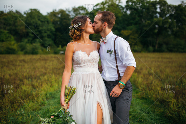 Bride and groom kissing in country field