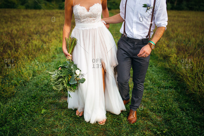 Bride and groom walking together in a field