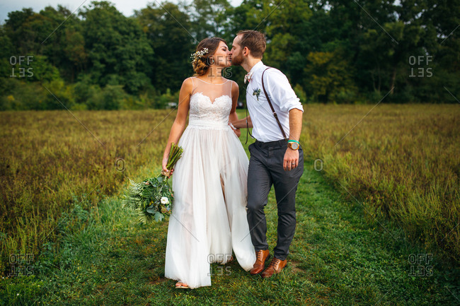 Bride and groom kissing in a field