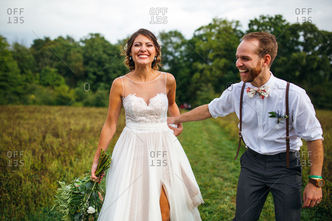 Happy bride and groom walking together in a field