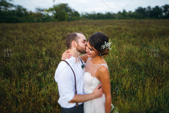 Groom kissing bride in a country field
