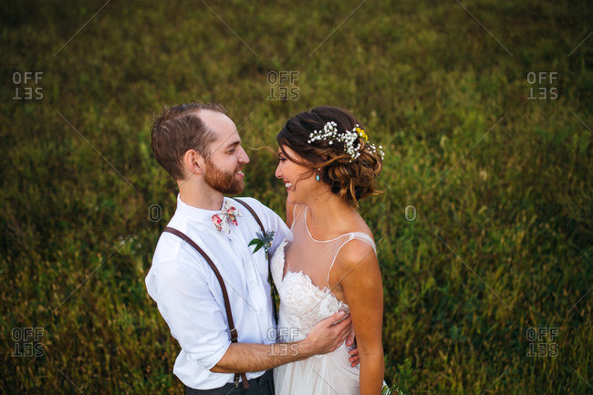 Happy bride and groom embraced in a field