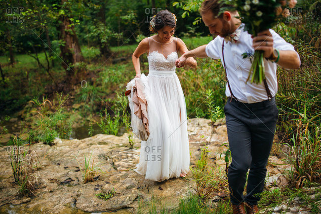 Groom helping bride walking on rocky ground