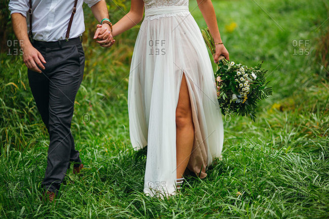 Newlywed couple walking together in a field