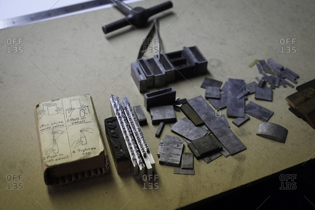 Metal blocks, type slugs and dummy page laid out in a printing shop