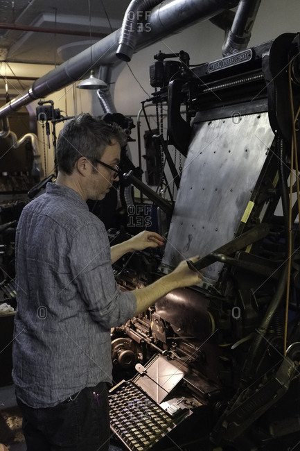 Brooklyn, USA - 24 February 2018: Printer working at an antique Linotype machine in workshop